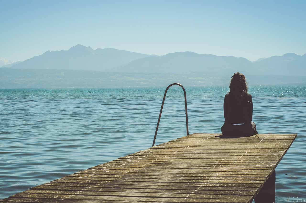 woman struggling with depression and addiction sitting by herself on the end of a dock