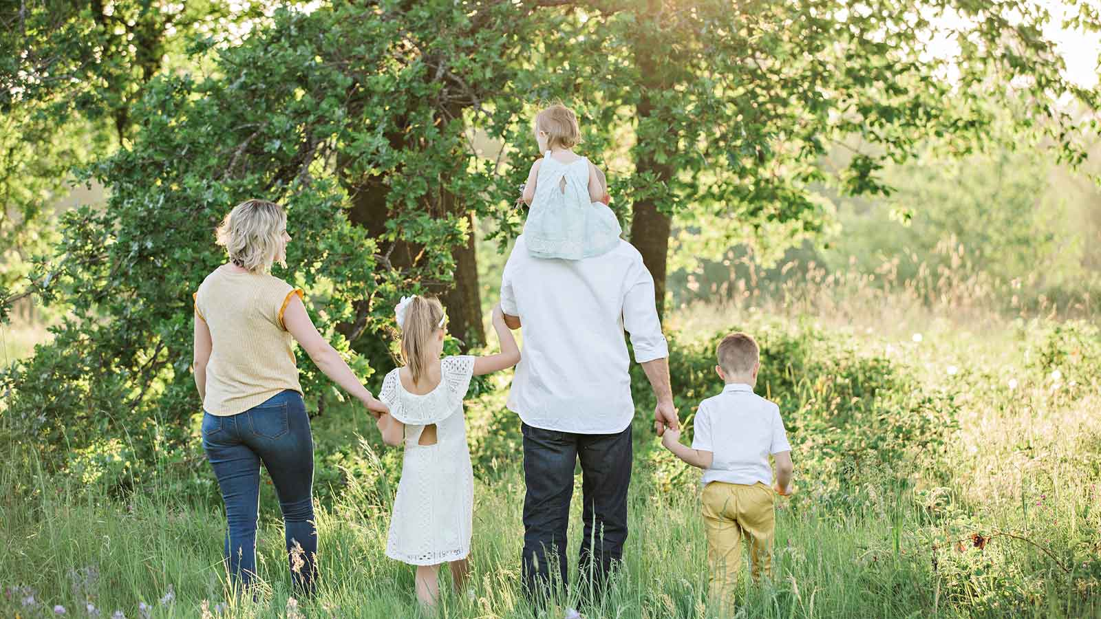 family of five walking together in a meadow
