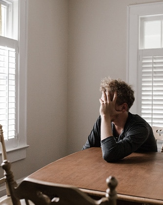 patient sits uncomfortably at dining room table while going through withdrawal at home