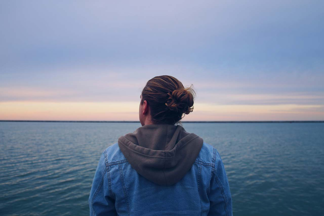 anxious man stares out at the ocean during dusk
