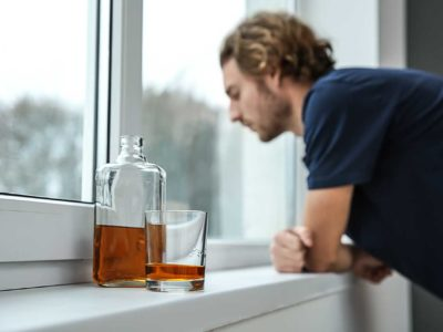 man looking out of his window with alcohol in the foreground
